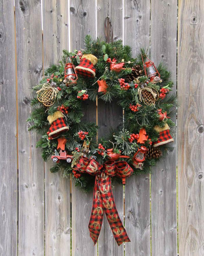 Weihnachtskranz aus Tannenzweigen mit roten Figuren und großer Schleife, Weihnachtsdeko für die Außentür