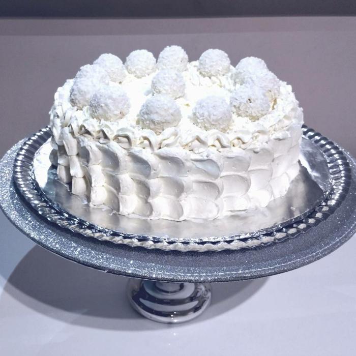 eine weiße Torte, bildschöne Dekoration von weißer Creme und Raffaello Pralinen, Raffaello Rezept