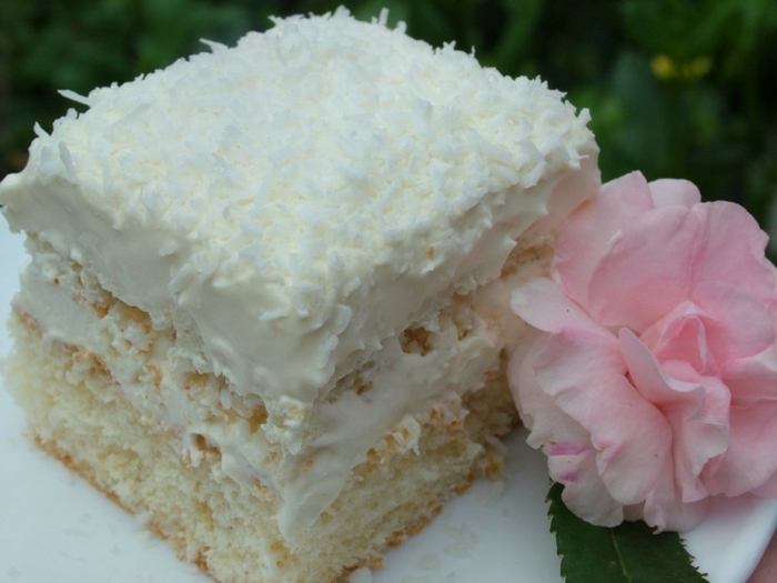 ein Stpck Torte neben einer rosa Blume aus Zucker, Torte selber machen mit Kokos und Creme