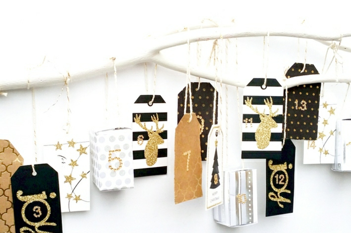 ein weißer Zweig mit kleinen Päckchen und Kärtchen für jeden Tag vor Weihnachten, Adventskaledner Ideen