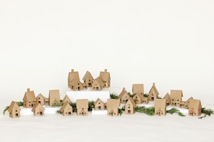 Adventskalender Ideen, ein Adventsdorf mit kleinen Häuschen, eine Lichterkette und Tannenzweige