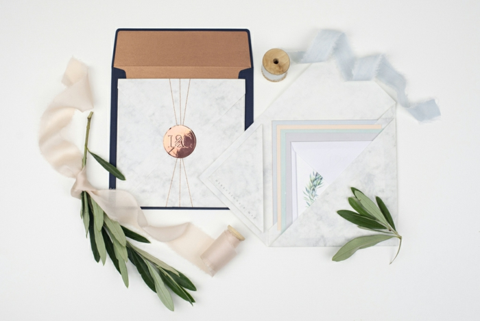 die fertige Einladung in den Briefumschlag stecken, Einladungskarten selber basteln mit den Initiallen des Brautpaars