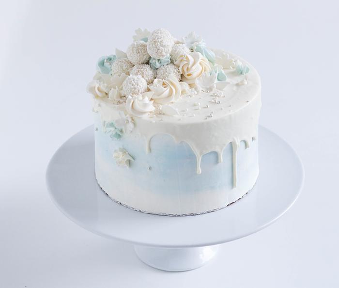 eine blaue Torte mit weißer Glasur, Raffaello Rezept zu Hochzeit, blaue und gelbe Blütten