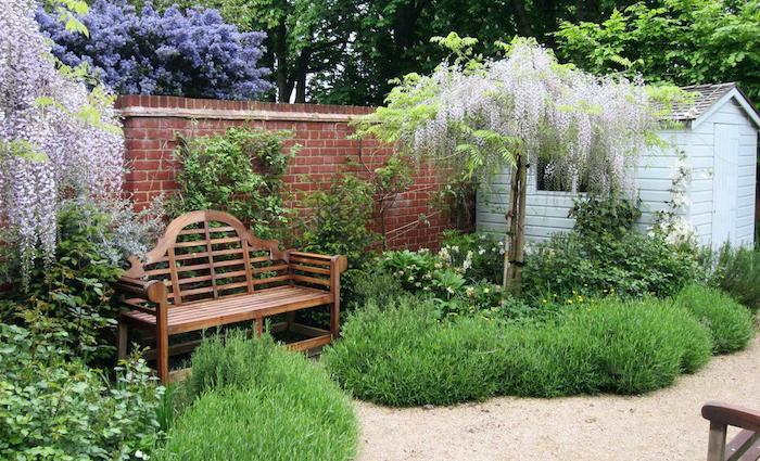 kleine braune bank in einem vorgarten mit violetten vorgarten bäumen und grünen pflanzen und ein kleines weißes haus aus holz