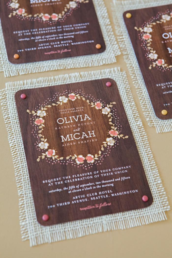 gravierter Holz als Einladungskarte drucken, ein Kranz von rosa Blumen dekoriert die Hochzeitseinladung