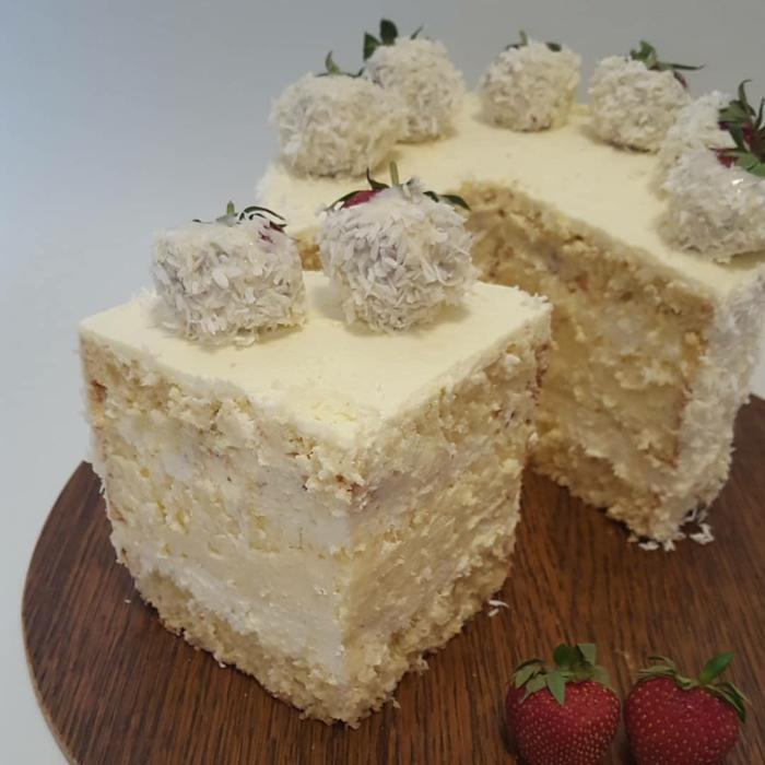 eine Torte mit Erdbeeren in Kokosraspeln bedeckt, Erdbeer Raffaello Torte mit gelber Creme