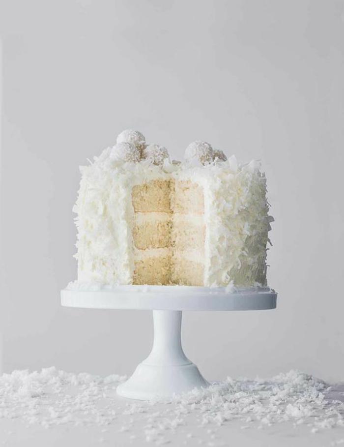 eine süße Torte mit drei Böden und weiße Creme, Kokosraspeln und Praline, Torte selber machen