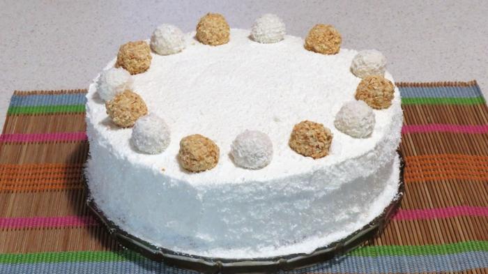 Raffaello Torte mit schneeweißer Creme und zwei Arten von Pralinen als Deko, Torte selber machen
