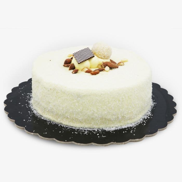 weiße Torte mit Pralinen als Dekoration, Nüsse dazu, Torte selber machen mit Kokosraspeln
