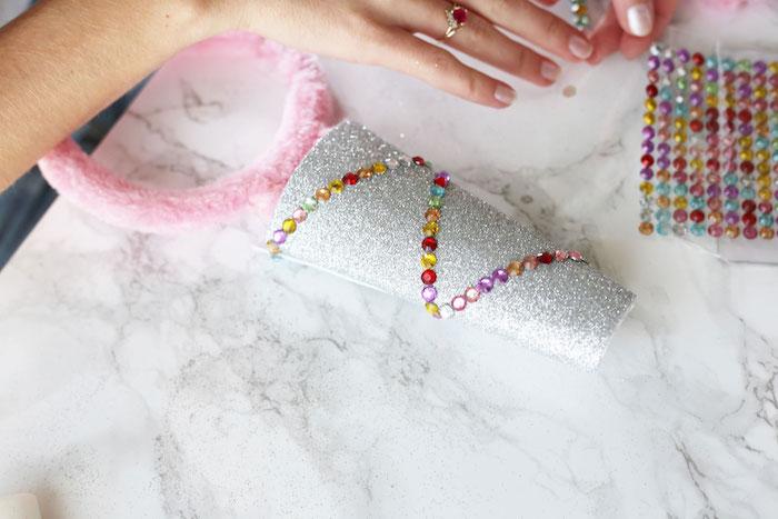 hände euner frau mit roten ringen und einem weißen nagellack, ein pinker haarreif und gefaltetes weißes papier mit glitter, materialien für diy einhorn kostüm