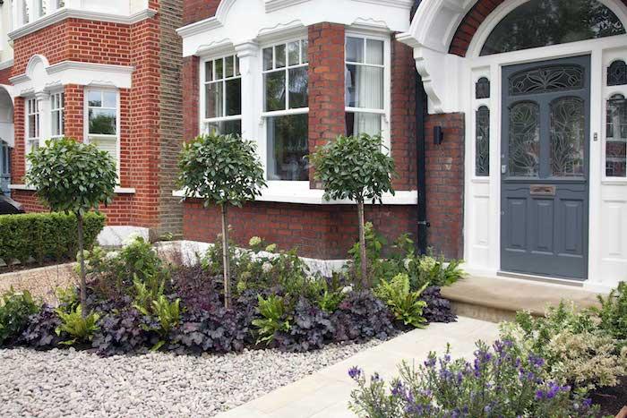 ein haus mit weißen fenstern und einem vorgarten mit grünen pflanzen, kleine bäume für den vorgarten