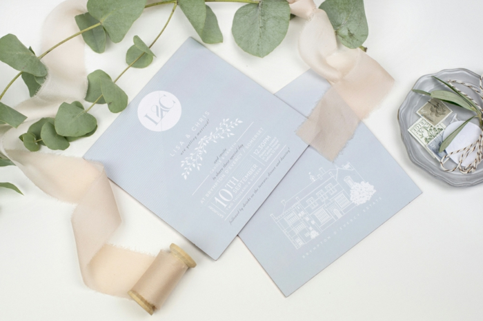 zwei blaue Einladungskarten selber basteln und mit rosa Schleife dekoriert, ganz kunstvoll