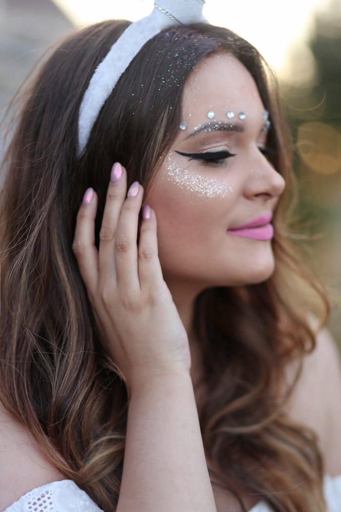 pinker nagellack einer jungen frau mit gesicht mit einhorn schminke mit glitter und lippen mit violettem lippenstiift, ein weißer einhorn haarreif