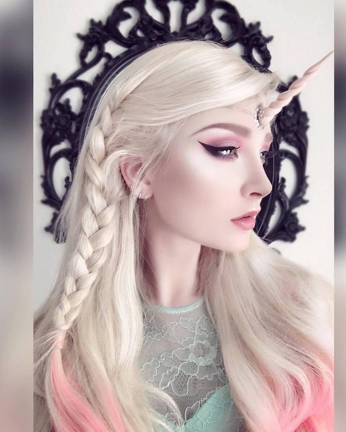 junge frau mit einem langen blonden haar und mit einer einhorn schminke mit schwarzem lidstrich und violetten lidschatten und einem langen pinken horn, einhorn schminken anleitung