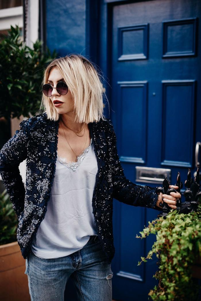 blonder bob mit dunklen ansätzen, moderne frau mit coolem outfit, runde brille, blazer mit silbernen elementen, seidentop, jeans und absatzschuhe