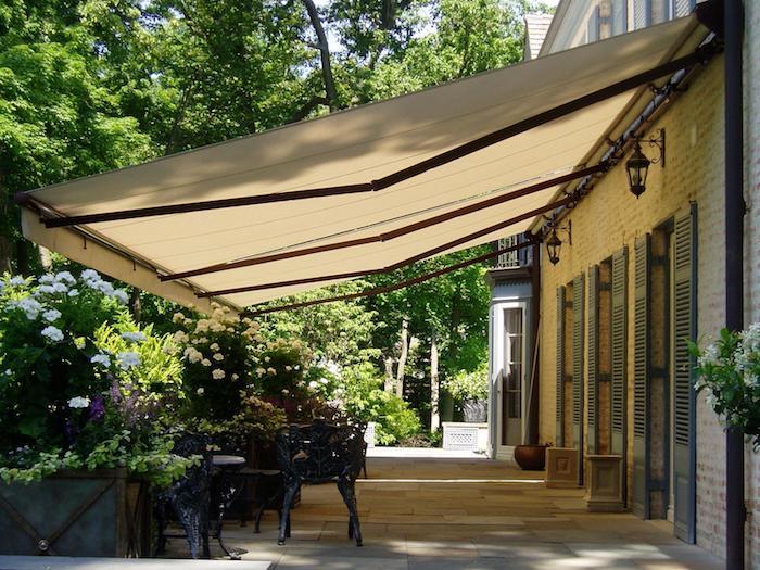 ein hazs mit terrasse mit stühlen und einer markise