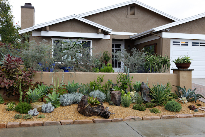 beiges haus mit einem vorgarten mit orangen kleinen vorgarten steinen und grünen vorgarten pflanzen mit grünen blättern, kleine bäume für den vorgarten