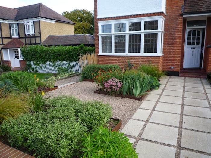 vorgarten mit steinen, ein haus mit weißen fenstern und einer weißen tür, gartenweg anlegen, violette und gelbe blumen