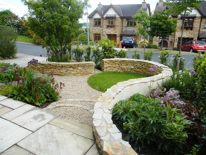 ein zaun aus steinen und ein moderner vorgarten mit kleinen grünen bäumen und violetten blumen, vorgarten modern gestalten