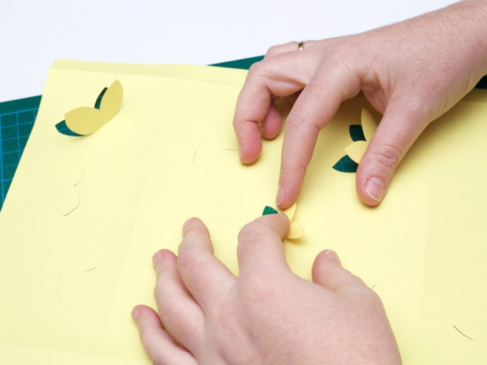 aus gelben Karton Laterne basteln, kleine Schmetterlinge ausschneiden, damit das Licht durchdringt
