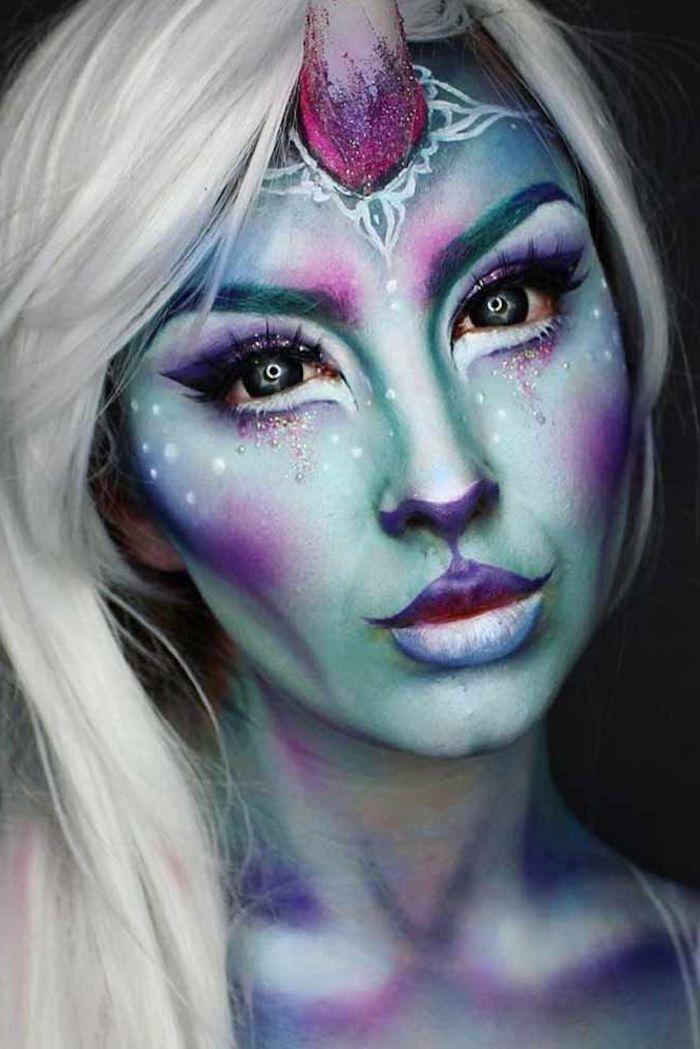 frau mit langem weißen haar und gesicht mit einhorn schminke mit glitter und grünen und violetten lidschatten, halloween kostüm mit einem großen violetten horn, einhorn kostüm selber basteln