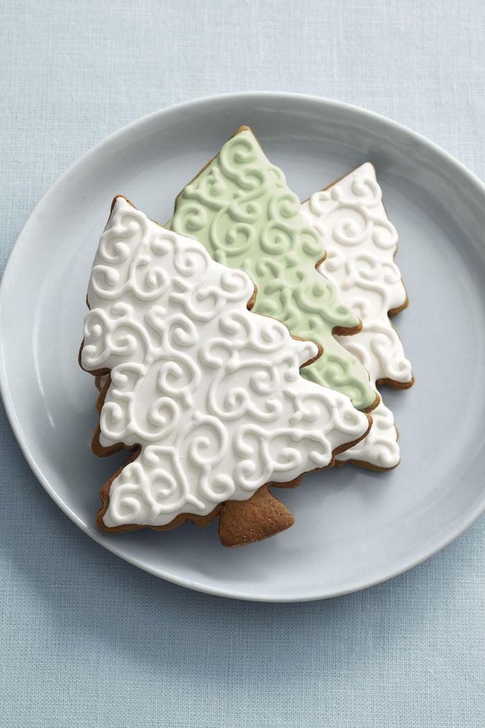 Weihnachtsplätzchen in Form von Christbäumchen, mit weißer und grüner Glasur dekorieren