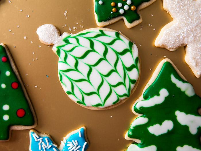 Leckere Weihnachtsplätzchen zum Ausstechen, weiße Christbaumkugel mit grünen Streifen