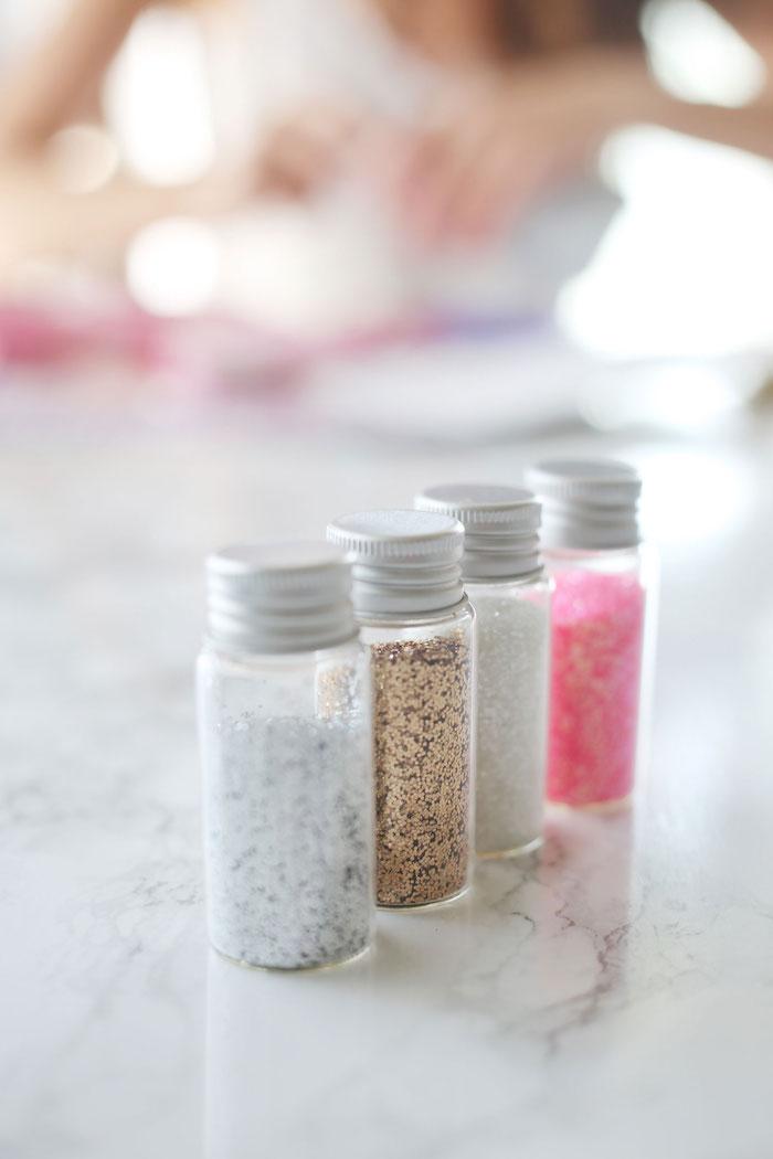 weißer tisch und kleine flaschen mit glitzer für eine halloween einhorn schminke, schminken einhorn anleitung