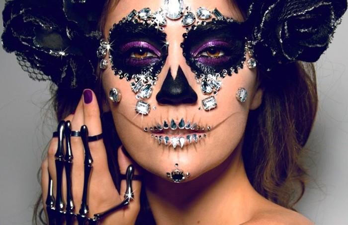 effektvolle zombie schminken, lila und schwarz augen make up und viele steine auf dem gesucht kleben, ring als skellet