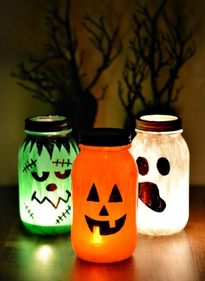 Kinderlaterne basteln, weiße, orange und grüne Ungeheuer zu Halloween, die die gruselige Nacht beleuchten