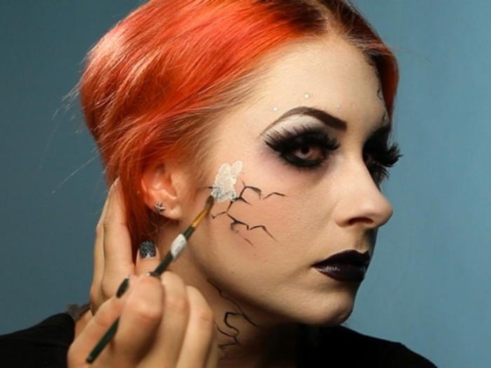 halloween schminken kinder, eine rothaarige frau zeigt wie sie sich selbst schminkt, pinsel weiße farbe, schwarze lippen