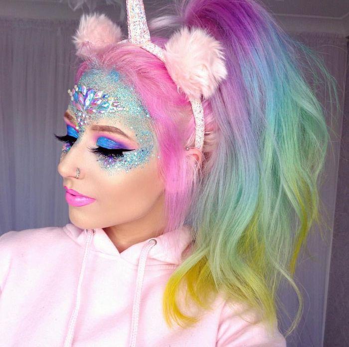 halloween kostüm frau, eine junge frau mit regenbogenfarbenem haar und einer einhorn frisur, einhorn schminken mit glitzer und violetten lidschatten und pinken lippen