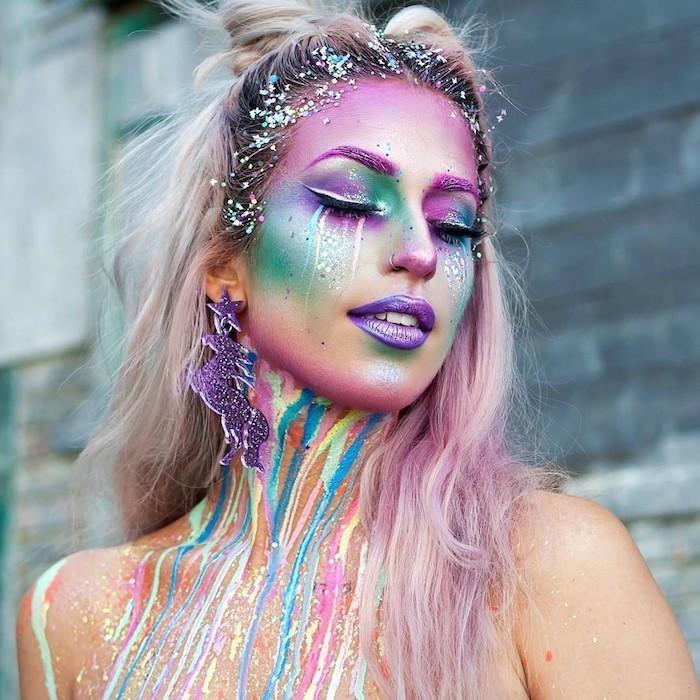 eine bunte einhorn schminke mit violetten lippen und violettem lidschatten und violetten einhorn ohrringen mit violetten sternen, regenbogenfarbene einhorn frisur