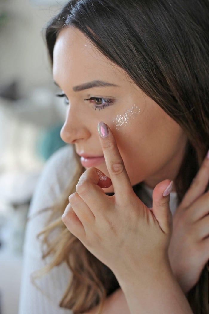 eine frau mit hand mit pinkem nagellack und eine schminke mit glitzer, frau mit braunem haar, einhorn schminken anleitung schritt für schritt