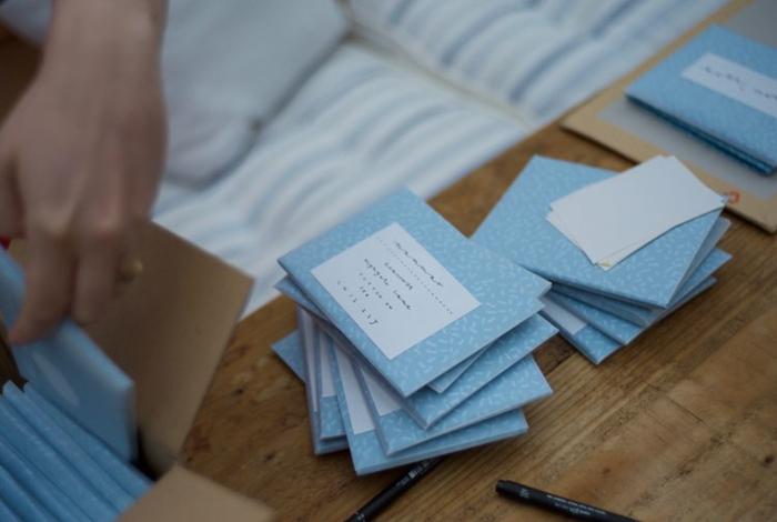 viele kleine blaue Briefumschläge mit den Adressen der eingeladenen zur Hochzeit, Einladungskarten selber basteln