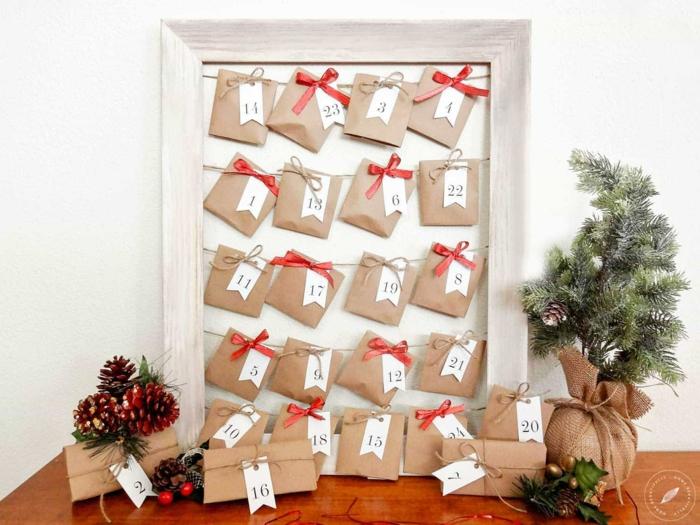 ein weißer Rahmen, von dem kleine braune Tüte hängen, mit rote Schleifen dekoriert, Adventskalender basteln