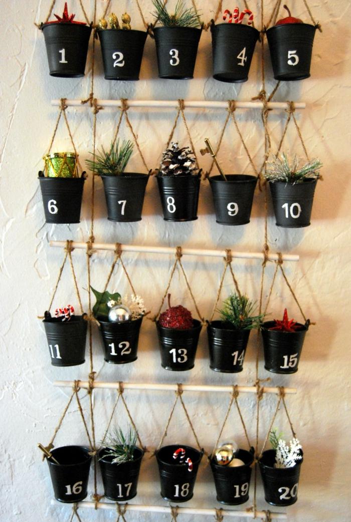 kleine schwarze Eimer mit Nummern, auf vier Stöcke gehängt, voller kleine Geschenke, Adventskalender selber basteln