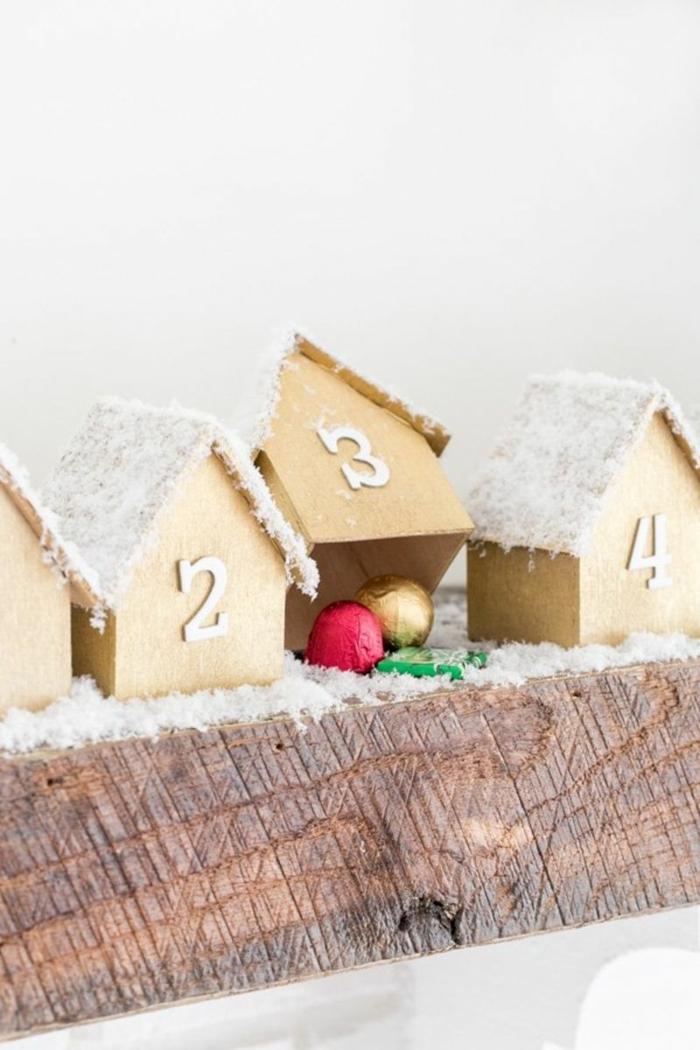 süßer Adventskaleder befüllen mit Süßigkeiten, Pralinen in roter und gelber Farbe, kleine Häuschen mit Nummern