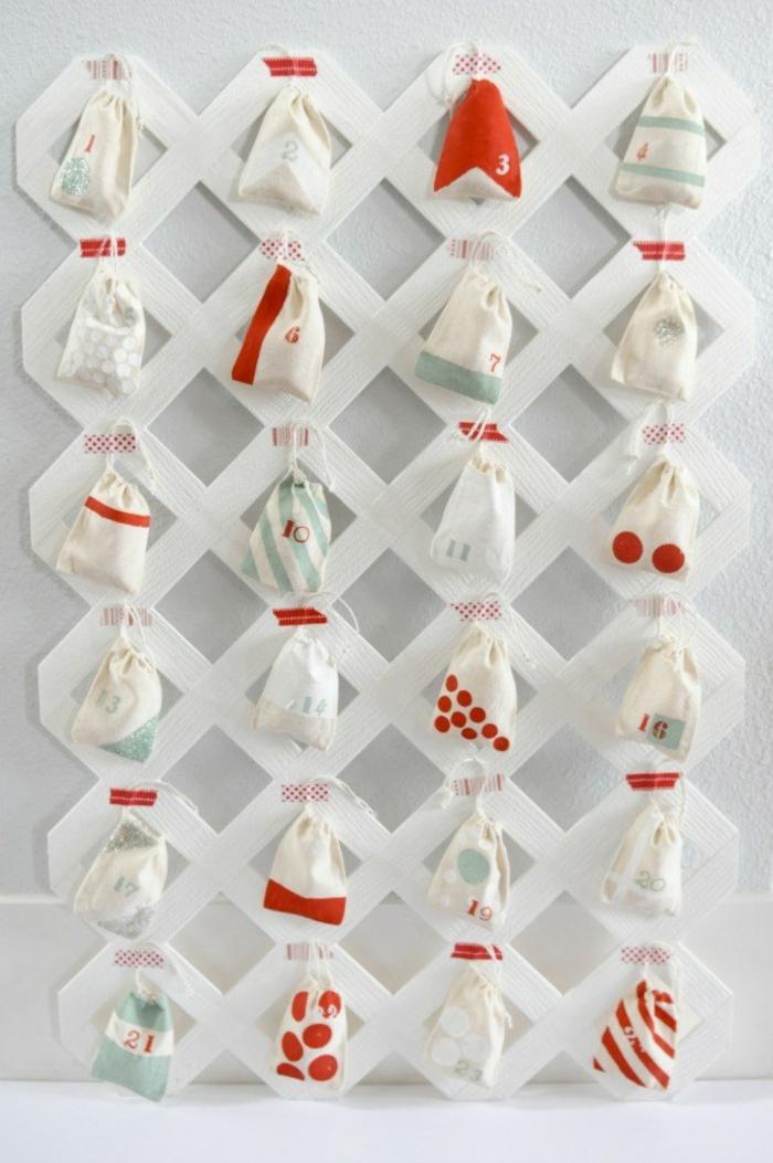 eine Netz aus Holz, wo der Adventskalender hängt, Weihnachtskalender basteln in weißer und roter Farbe