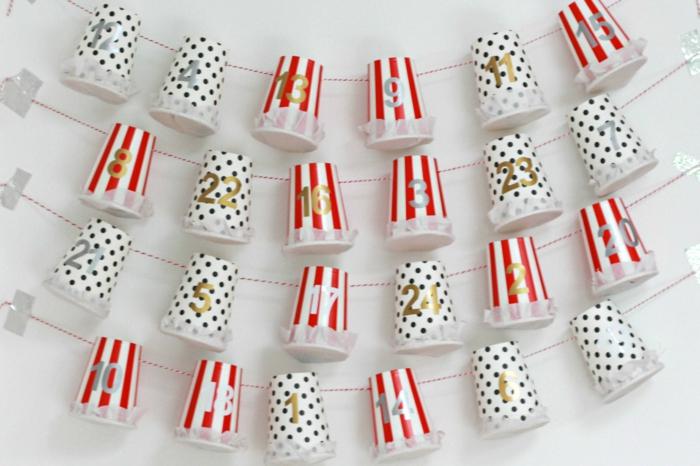 vier Fäden, auf denen kleine Plastikbecher hängen, Weihnachtskalender basteln in weinahtlichen Farben, Rot und Weiß
