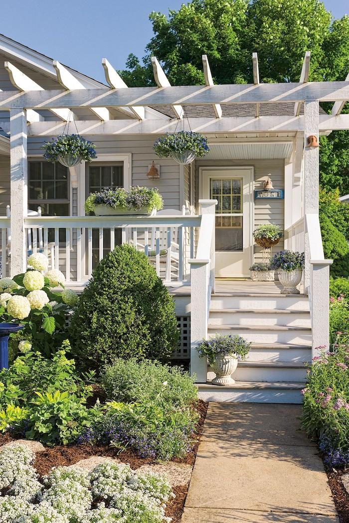 ein weißes haus mit einer weißen terrasse mit blumentöpfen mit violetten blumen und vorgarten pflanzen und ein gartenweg und wdeiße rosen mit grünen blättern