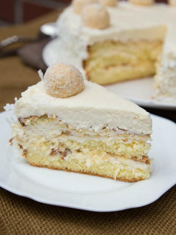 ein Stück Kuchen, beige Glasur von Nüssen, Kokosraspeln darin, Raffaello Torte
