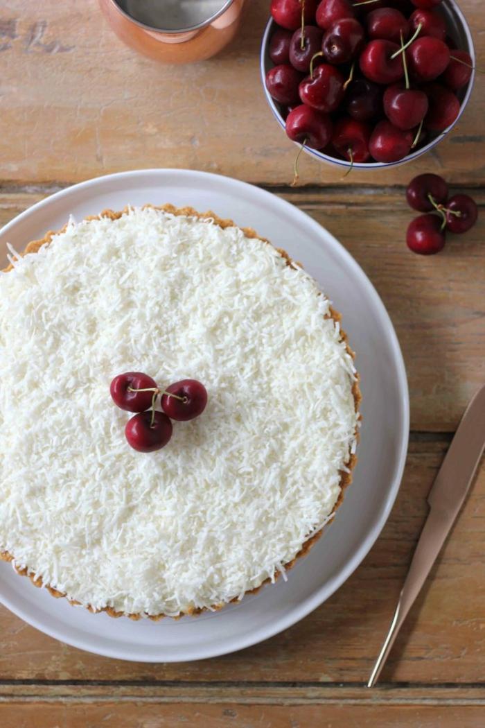 eine kleine Torte mit Kirschen dekoriert und mit Kokosraspeln bedeckt, Raffaello selber machen