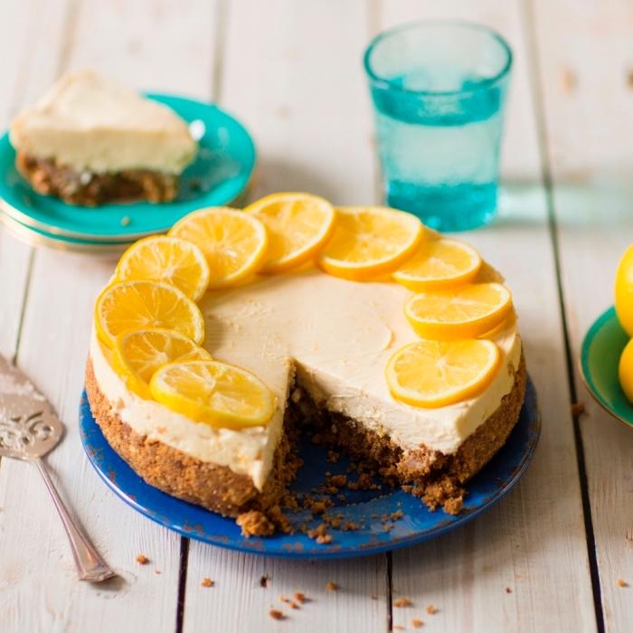 blauer teller, torte mit zitronen, kuchen mit butterkeksen, glas vaser, spachtel