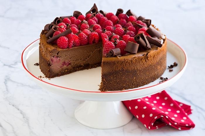 weißer tortengestell, kuchen mit butterkeksen, schokolade und himbeeren, geburtstagstorte