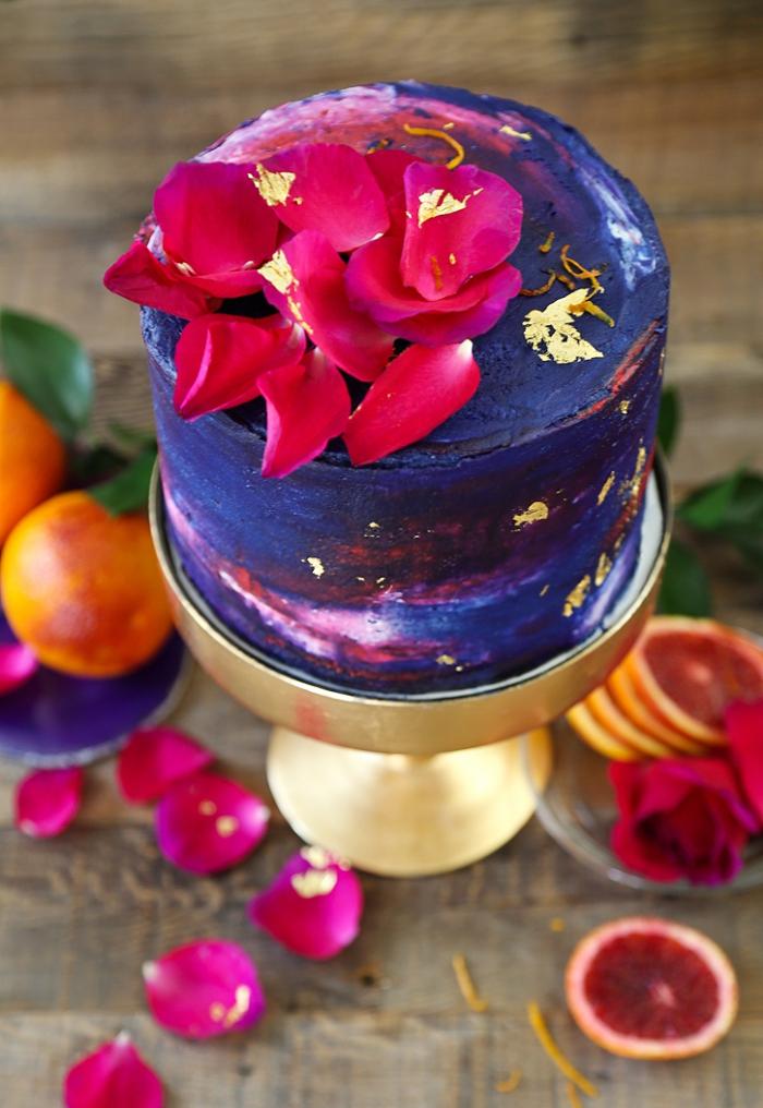 kuchen verzieren, geburstagstorte dekoriert mit creme in lila, blau und rot und rosenblätter, torte mit roter orange