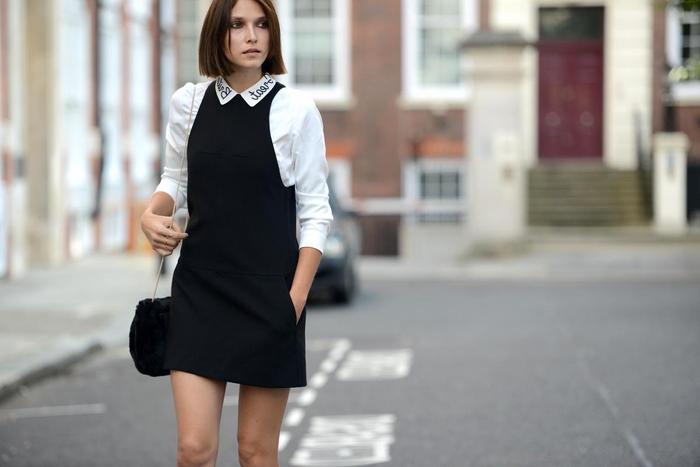 bob frisuren kurz stufig, eine frau mit schwarzem kleid mit perlen verziert und weiße weste, haare über den schultern, kleine tasche