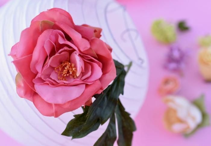 Laterne basteln, eine schöne rosa Rose zu der weißen Laterne als Dekoration befestigt