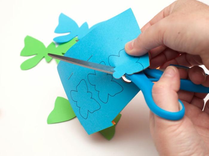 blaues Papier aus dem Schmetterlinge ausgeschnitten sind, Dekoration für Laterne basteln