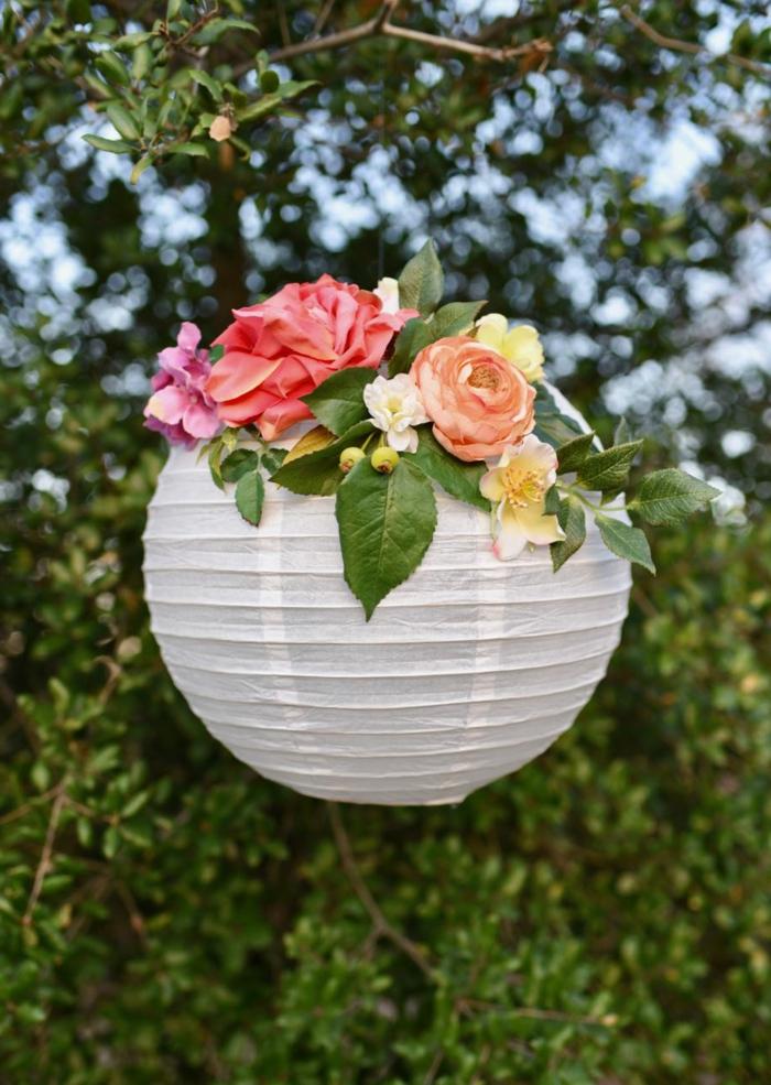 eine weiße Laterne mit bunten künstlichen Blumen dekoriert im Garten, Lampion basteln